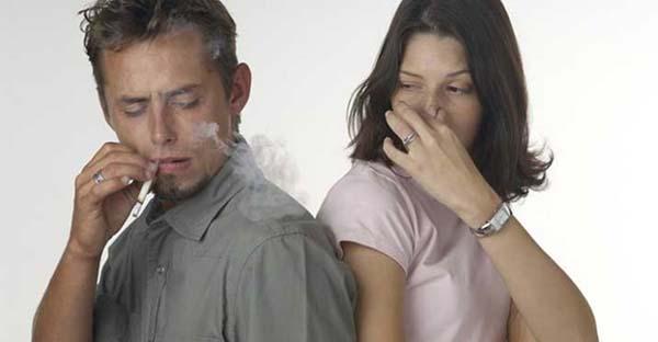 Seorang wanita menghindari asap rokok