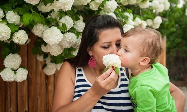 Ibu dan anak menyium bunga